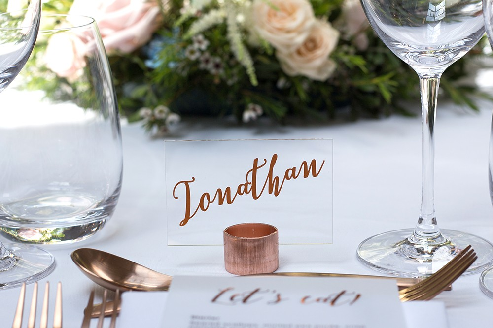 Acrylic place names in copper pipe stand with metallic copper vinyl letters wedding stationery and styling by www.rosepaperscissors.com