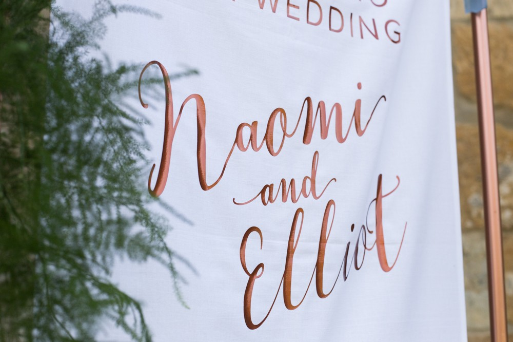 Fabric wedding welcome sign in copper pipe stand with metallic vinyl lettering -Blackwell Grange Wedding - Stationery, Styling and photography by www.rosepaperscissors.com