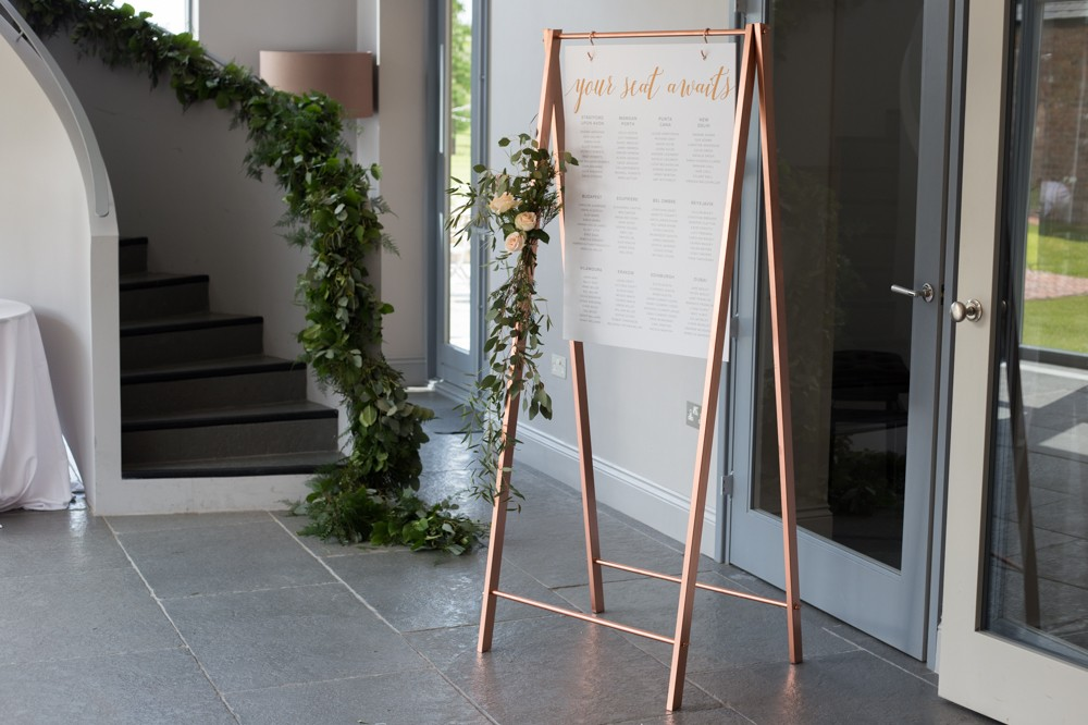 Copper table plan stand with metallic vinyl hanging board - wedding styling and stationery by www.rosepaperscissors.com
