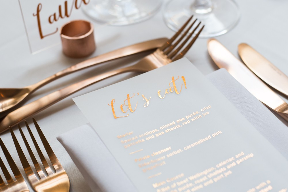 Acrylic place names in copper pipe stand and transparent vellum copper foil menus at Blackwell Grange- wedding stationery and styling by www.rosepaperscissors.com